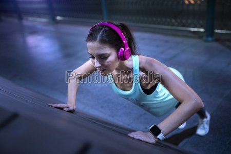young woman with pink headphones doing