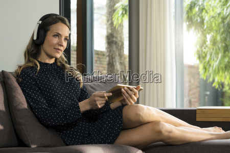woman with tablet and headphones relaxing