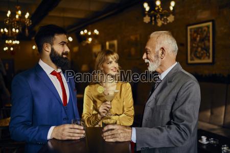 two elegant men and woman socializing