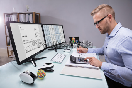 side view of a businessman calculating
