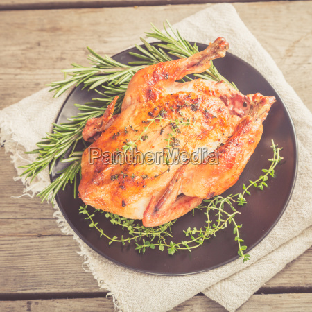 fried whole chicken with herbs over