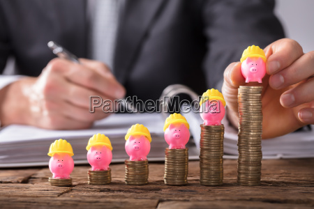 businessperson placing piggybank on increasing stacked