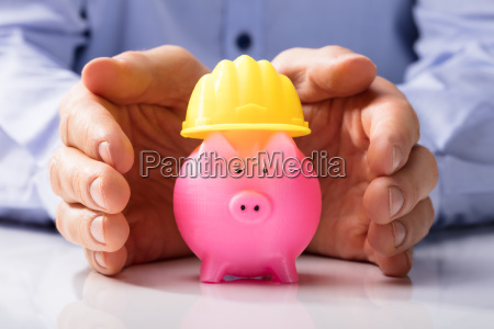 person protecting hard hat and piggy