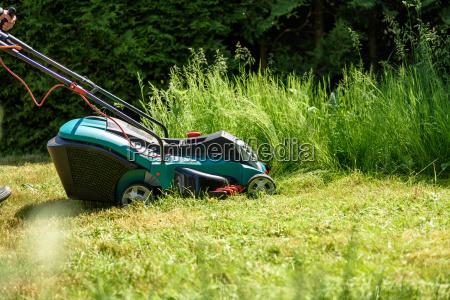 man cutting grass with an