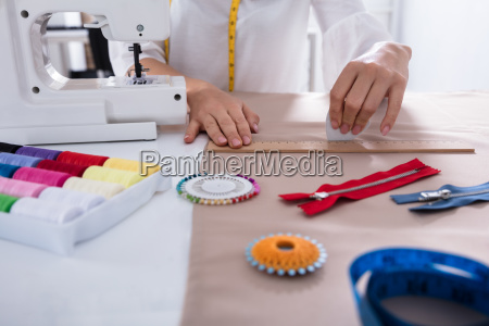 fashion designer measuring fabric with ruler