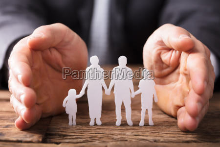 businesspersons hand protecting family figures