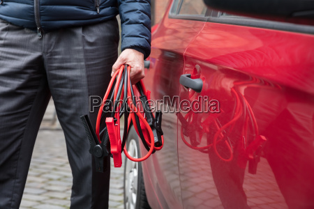 persons hand holding jumper cables