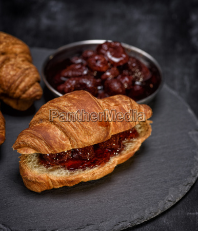 baked croissant with strawberry jam on