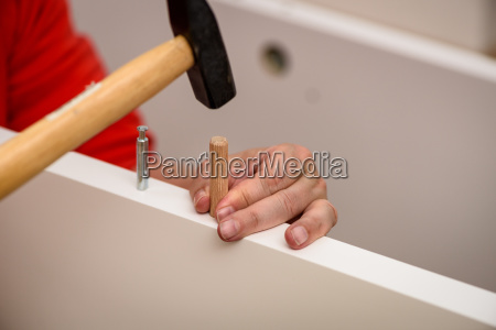 close up on hands hammering a
