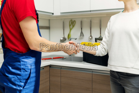 plumber and woman shaking hands after