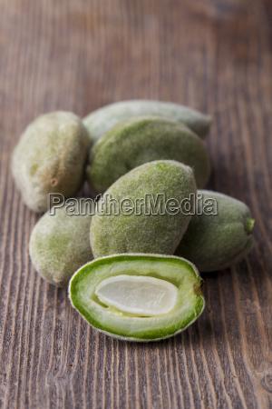 green almonds on dark wood