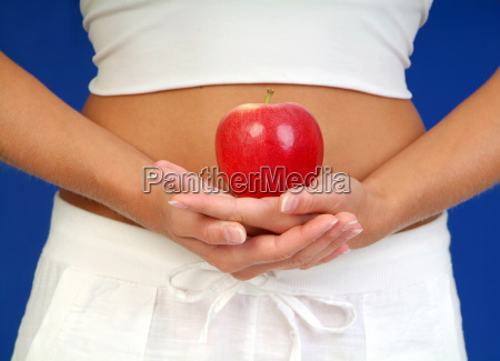 woman holds apple in front of