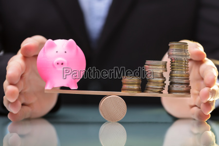 businessperson protecting piggy bank and stacked