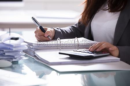 businesswoman calculating invoice