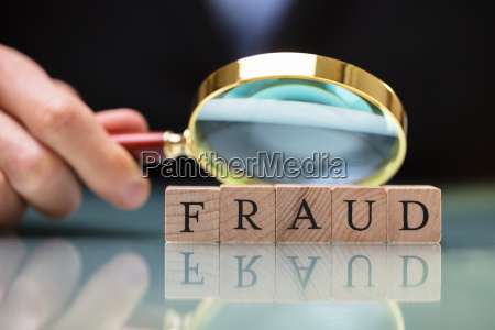 businessperson holding magnifying glass over fraud
