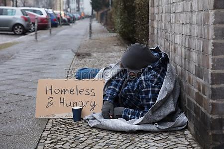 male beggar lying on street
