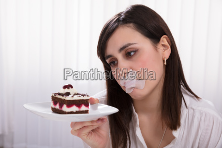 woman holding slice of cake on