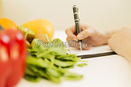 nutritionist woman writing diet plan on