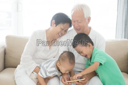 grandparents and grandchildren using smart phones
