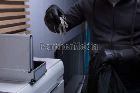 robber wearing gloves stealing jewelry