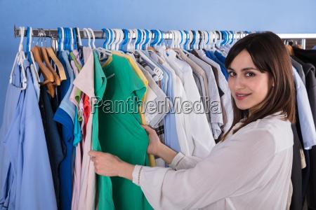 woman choosing clothes on clothes rail