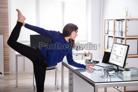 young businesswoman doing yoga