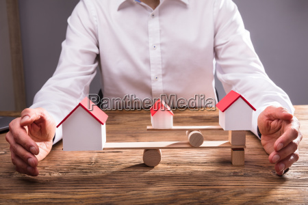 businesspersons hand covering balance between house