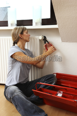 young woman repairs the thermostat at