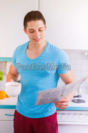 young man reads reading newspaper in