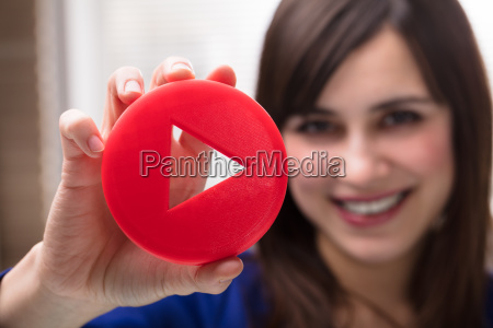 womans hand holding play icon