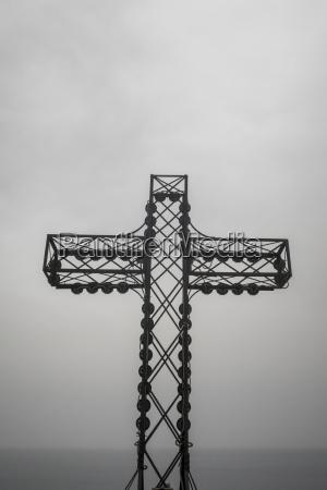 metal cross overlooking the sea at
