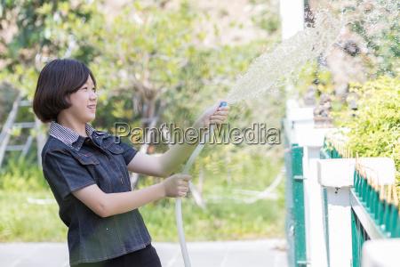 women standing watering a tree