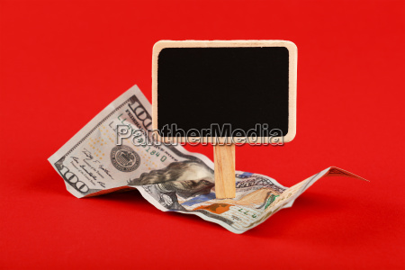us dollar banknote and blackboard sign