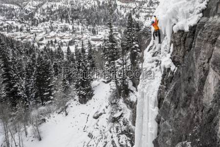 man ice climbing up frozen cascade