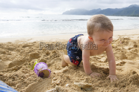 baby boy playing in sand on