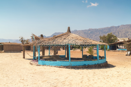straw huts on beach during daytime