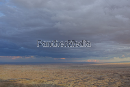 storm clouds over barren landscape of