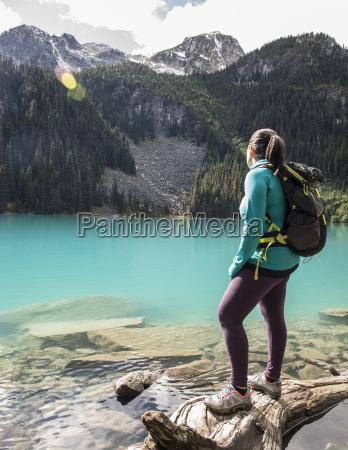 female backpacker standing on shore of
