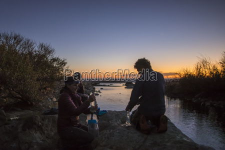 three hikers resting and refilling water