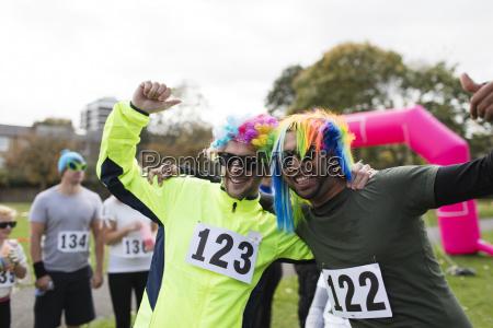 portrait playful male runners wearing wigs