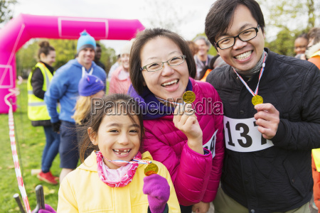 portrait enthusiastic family runners showing medals