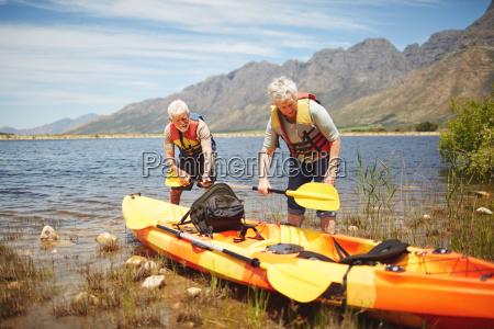 active senior couple preparing kayak at