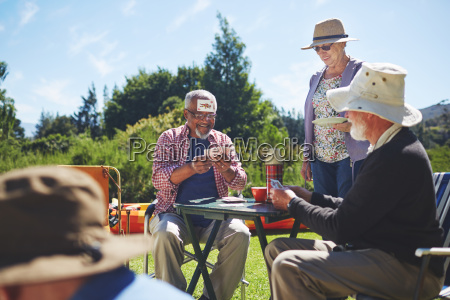 playful active senior friends playing cards