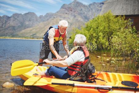 active senior couple kayaking on sunny