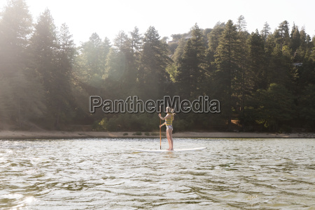 woman paddleboarding on sunny tranquil lake