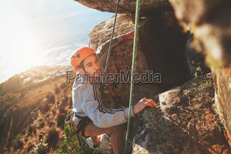 focused male rock climber climbing rock