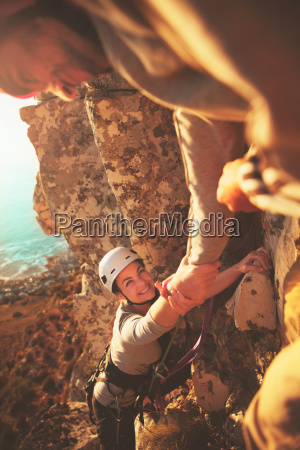 smiling female rock climber reaching for