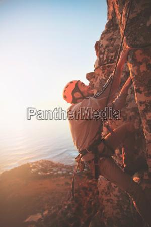 male rock climber scaling rock