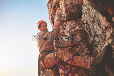 focused male rock climber hanging from