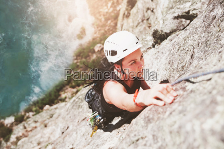 focused determined female rock climber scaling